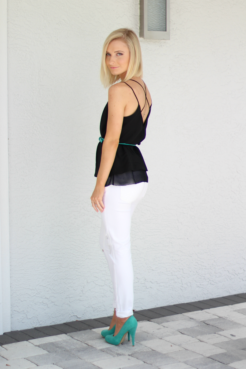 White jean, teal accessories, and a criss cross back top